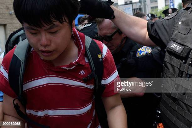Anlin Wang is struck on the back of his head by an officer as Police clears protestors from blocking the loading dock of a Department of Homeland...