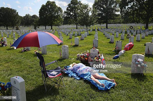 Ann Adams lies atop the grave of her son Army Sgt Andrew Baddick at the National Cemetery on Memorial Day on May 28 2012 in Arlington VA Baddick died...