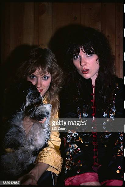 Ann and Nancy Wilson of the rock group Heart hold a dog