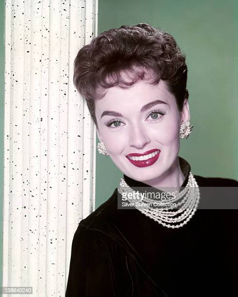 Ann Blyth US actress wearing a black jumper with a pearl necklace and matching earrings in a studio portrait against a green background circa 1955