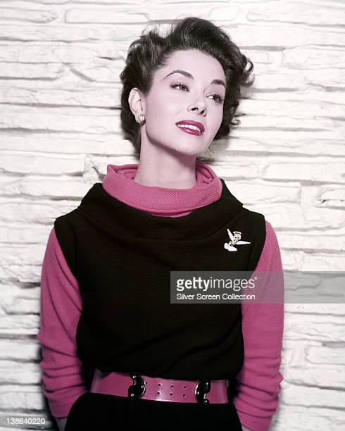 Ann Blyth US actress wearing a red jumper beneath a black sleeveless dress with a red belt and silver brooch in a studio portrait against a white...