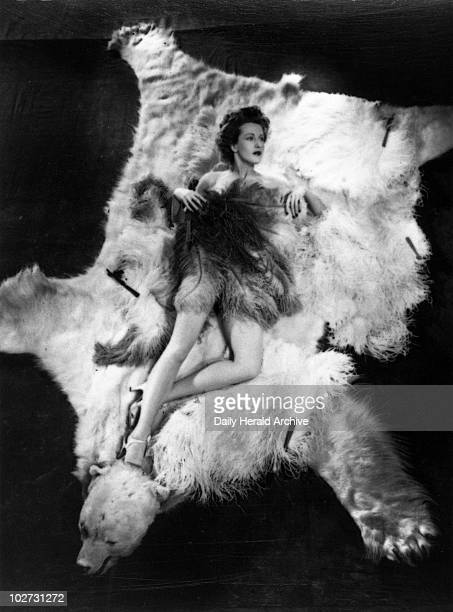 Ann Crawford 1944 Film actress and pinup girl lying on a bearskin rug naked but for an ostrichfeather fan