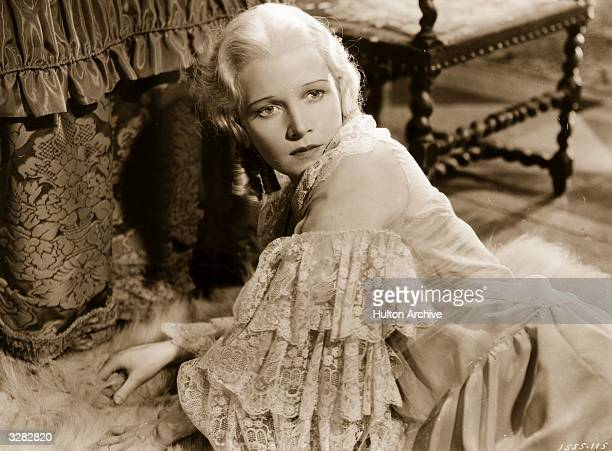 Ann Harding the screen name of Dorothy Gatley the American actress wearing a beautiful lace dress as she lies sprawled on the floor in a scene from...