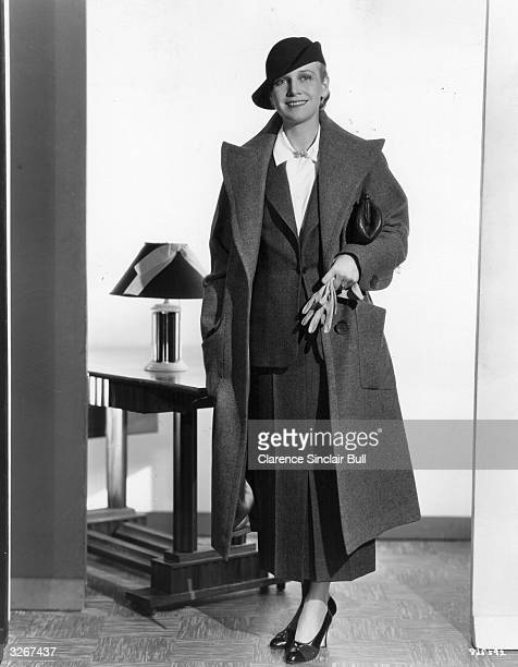 Ann Harding the stage name of Dorothy Gatley the American leading lady wearing a tailored suit and top coat in fine grey wool with wide lapels...