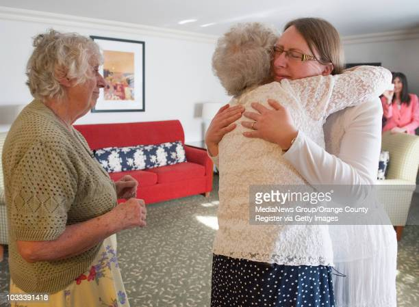 Ann Hunt left of Aldershot England looks on as her twin sister Ann Hamel hugs Hunt's daughter Samantha Stacey in a reunion at the Fullerton Marriott...