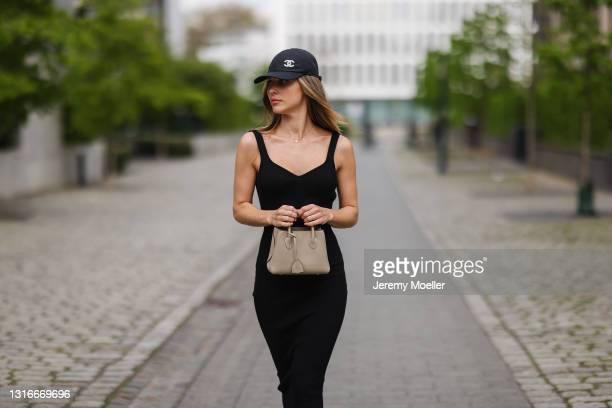 Ann Kathrin Götze wearing black Bazilika midi dress, black Chanel logo cap and greige Mini Mia tote Bonaventura bag on May 03, 2021 in Dusseldorf,...