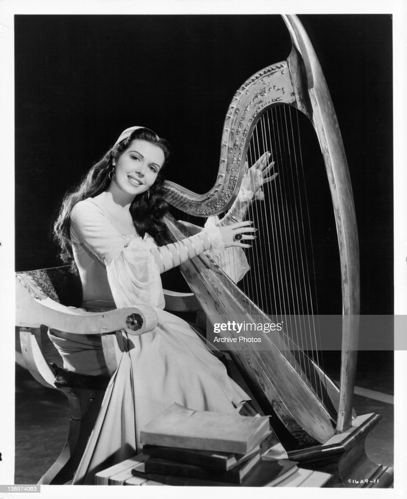 Ann Miller plays the harp in a scene from the film 'Kiss Me