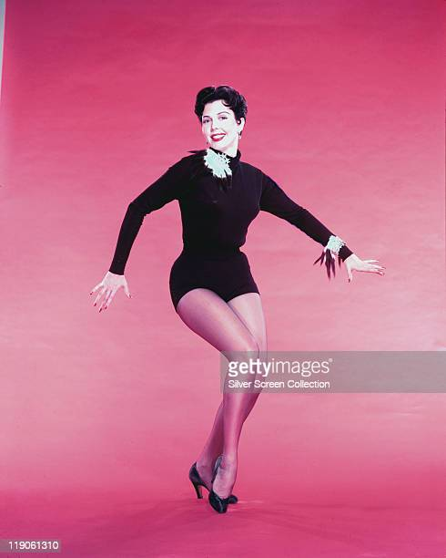 Ann Miller US actress holding a dance pose against a pink background circa 1950
