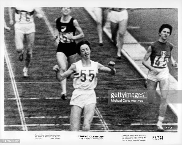 Ann Packer crosses the finish line in a scene from the film 'Tokyo Olympiad' 1965