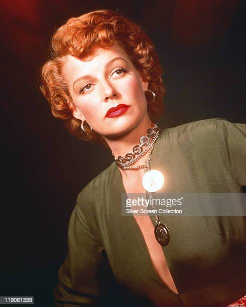 Ann Sheridan US actress in a studio portrait wearing a green top and a silver necklace with pendants with a glare reflectiing off one of the pendants...