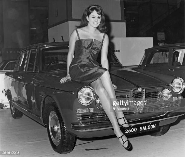 Ann Sidney, winner of the 1964 Miss World contest as Miss United Kingdom, sitting on an Alfa Romeo 2600 saloon car at the Motor Show in Earl's Court,...
