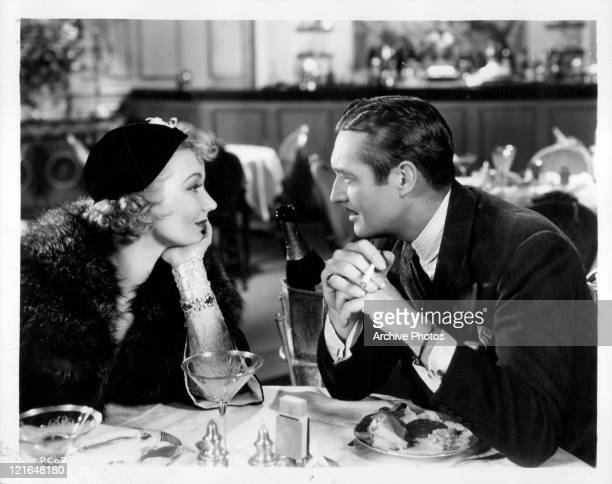 Ann Sothern and Edmund Lowe look into each other's eyes over a bottle of champagne in a scene from the film 'Grand Exit' 1935