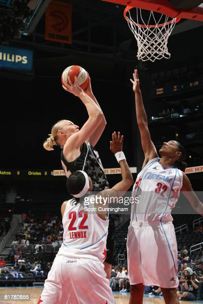 Ann Wauters of the San Antonio Silver Stars goes to the basket under pressure against Stacey Lovelace and Ivory Latta of the Atlanta Dream during the...