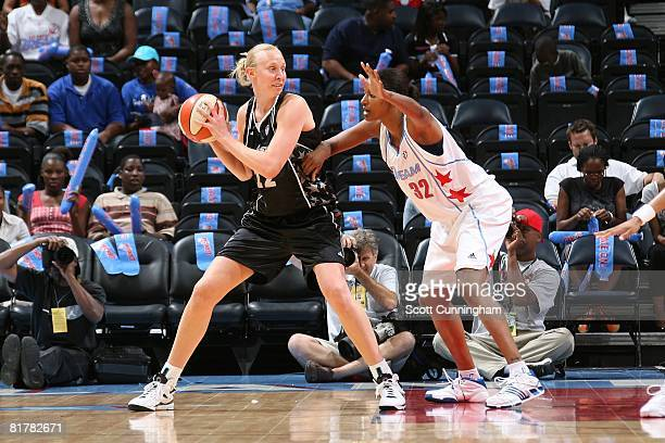Ann Wauters of the San Antonio Silver Stars looks to the pass the ball under pressure against Stacey Lovelace of the Atlanta Dream during the WNBA...