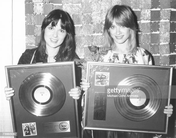 Ann Wilson and Nancy Wilson of the rock and roll band 'Heart' pose for a portrait holding gold records they were awarded by the RIAA for a milestone...
