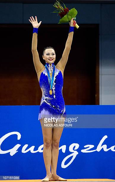 Anna Alyabyeva of Kazakhstan celebrates with her gold medal on the podium during the rhythmic gymnastics individual allaround final during the 16th...