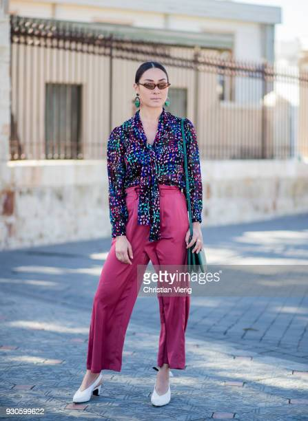Anna Aronov wearing blouse high waisted pants white heeled shoes sunglasses is seen during Tel Aviv Fashion Week on March 11 2018 in Tel Aviv Israel