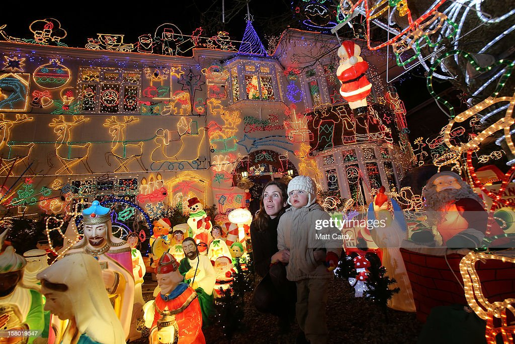 Anna Barclay and son Zac, 2, stop to look at Christmas festive lights that adorn a detached house in a suburban street in Melksham, December 8, 2012 in Melksham, England. The lights, a popular festive attraction, have returned to the town after a two-year absence and have raised thousands of pounds for charity for a local hospice, Dorothy House. The display, which is estimated to involve over 100,000 bulbs, worth over 30,000 GBP and even needed an up-rated electricity supply installed to cope with the additional power needed, is the brainchild of householder and electrician Alex Goodhind. This year, the display which Mr Goodhind began fifteen years ago now takes a team of professional electricians five weeks to complete, and even includes a snow machine.