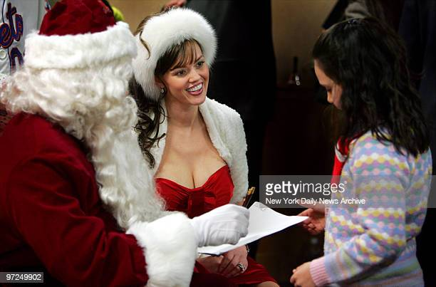 Anna Benson dressed as Mrs Claus helps her husband New York Mets' pitcher Kris Benson as he plays Santa Claus during the Mets' annual holiday party...