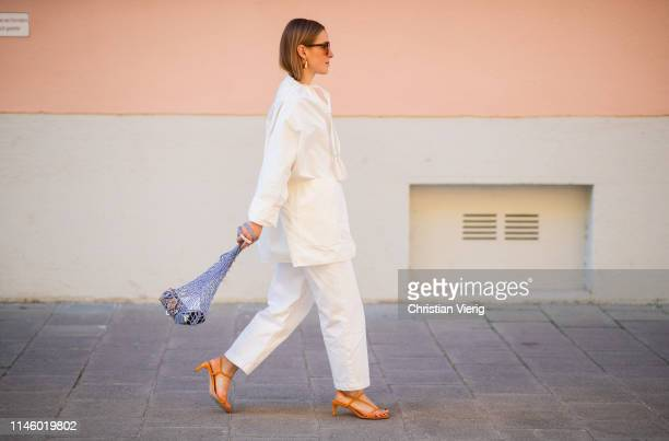Anna Borisovna is seen wearing net bag orange sandals sunglasses white top and white pants on April 18 2019 in Munich Germany