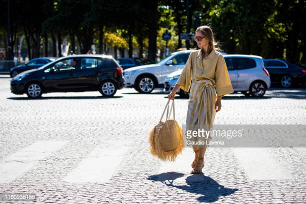 Anna Borisovna wearing a yellow shirt white and yellow striped skirt yellow sandals and straw bag is seen outside Chanel show during Paris Fashion...