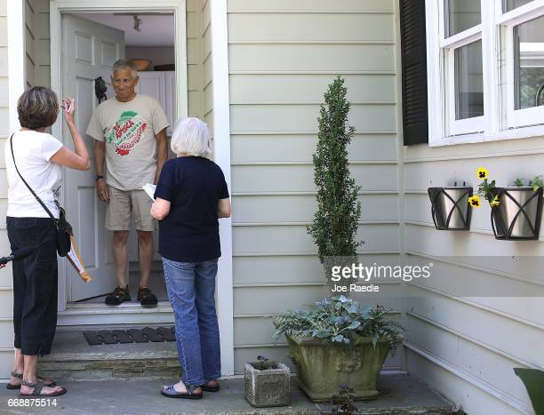 Anna Cay Robertson and Christina Ferguson speak with Randy Ellis as they canvass a neighborhood for Democratic candidate Jon Ossoff as he runs for...