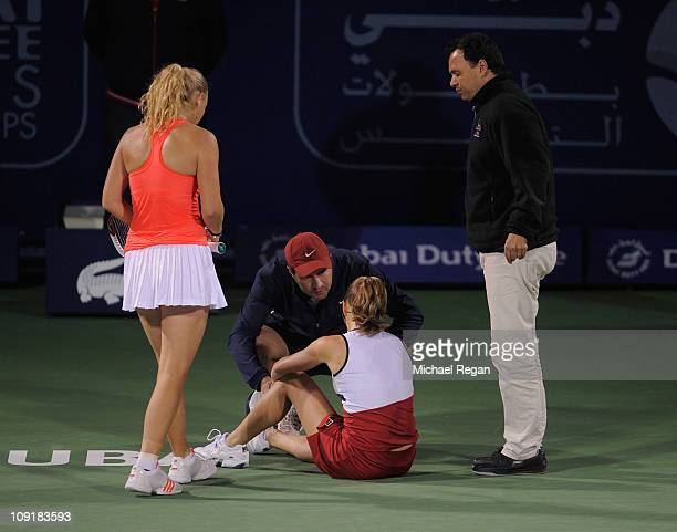 Anna Chakvetadze of Russia is treated by medical staff after collapsing during her Round 2 match against Caroline Wozniacki of Denmark during day...