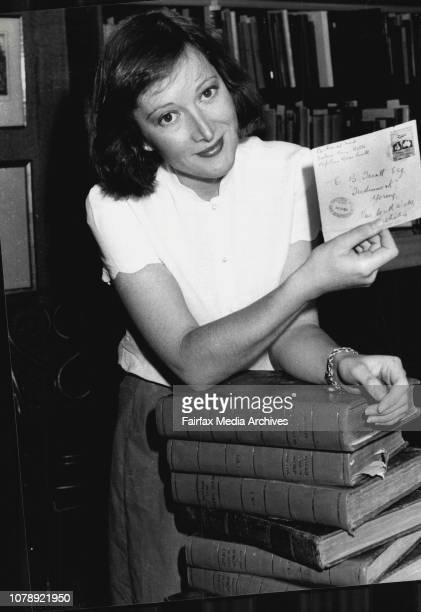 Anna Clark Anna Clark holding a rare stamp of Ross Smith Vignetih Also in picture is stack of early editions of books of Captain Cook's voyages...