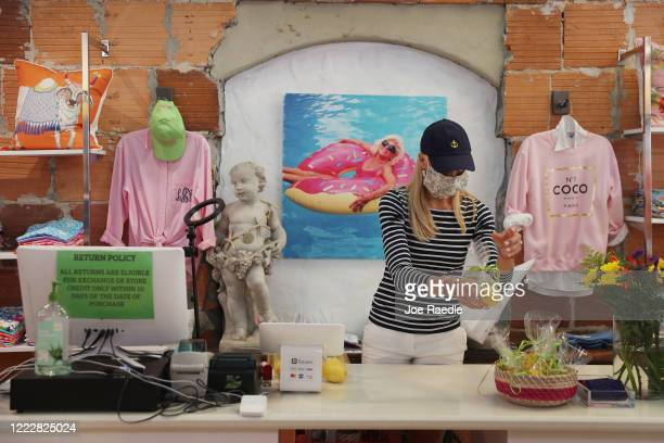 Anna Croxton prepares a free gift for customers at the Snappy Turtles store, as the state of Florida enters phase one of the plan to reopen the state...
