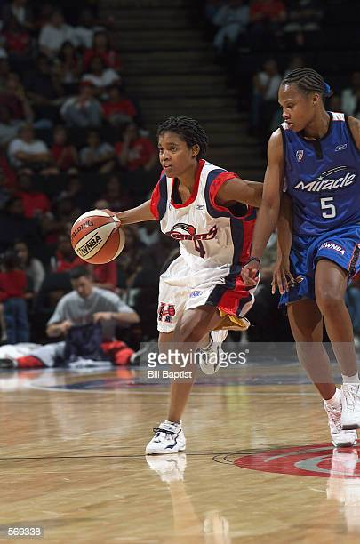 Anna DeForge of the Houston Comets drives past Elaine Powell of the Orlando Miracle during the WNBA game at Compaq Center in Houston Texas on May 21...