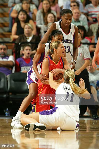 Anna DeForge of the Phoenix Mercury gets tied up between Erin Buescher and Chelsea Newton of the Sacramento Monarchs on August 23 2005 at Arco Arena...