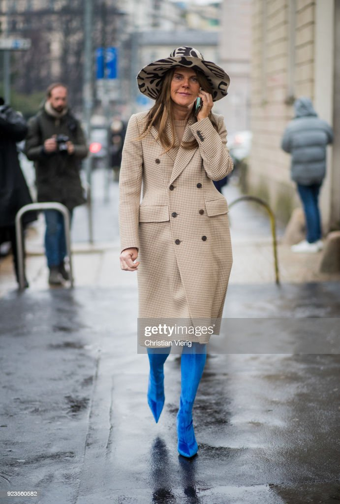 Anna dello Russo wearing beige coat, blue boots, hat seen outside Tods during Milan Fashion Week Fall/Winter 2018/19 on February 23, 2018 in Milan, Italy.