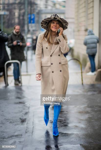 Anna dello Russo wearing beige coat blue boots hat seen outside Tods during Milan Fashion Week Fall/Winter 2018/19 on February 23 2018 in Milan Italy