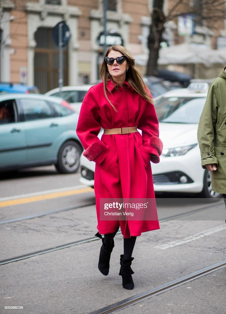 Anna dello Russo wearing red coat with brown belt, black ankle boots is seen outside Fendi during Milan Men's Fashion Week Fall/Winter 2018/19 on January 15, 2018 in Milan, Italy.