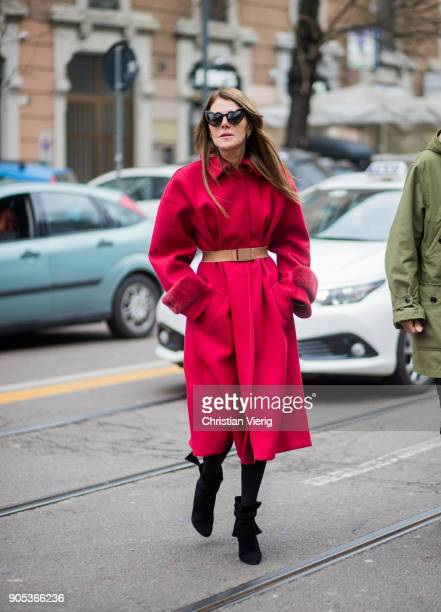 Anna dello Russo wearing red coat with brown belt black ankle boots is seen outside Fendi during Milan Men's Fashion Week Fall/Winter 2018/19 on...