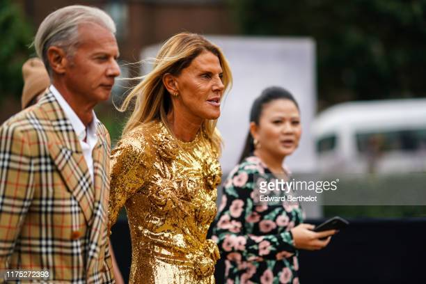Anna Dello Russo wears a golden shiny glitter dress with floral embroidery ; a guest wears a checked trench coat, outside Burberry, during London...