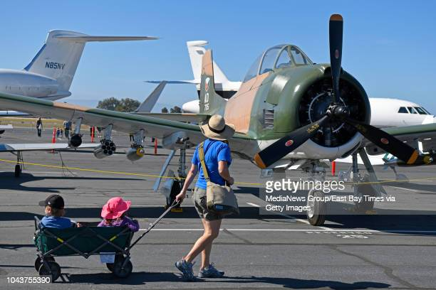 Anna Dix of Castro Valley pulls her children Nico and Kadence as they walk past a North American Aviation AT28D airplane owned by Steve Scott of...