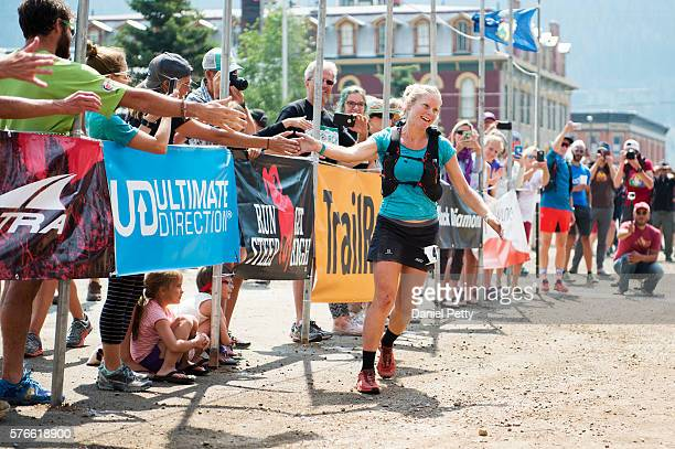 Anna Frost highfives hands of spectators at the finish line of the Hardrock 100 ultra distance run through the San Juan Mountains on July 16 in...