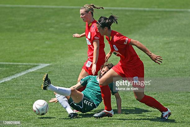 Anna Green and Abby Erceg of Adelaide defends against a shot at goal by Ashleigh Sykes of Canberra during the round one W-League match between...