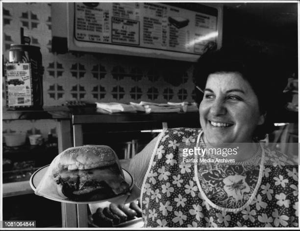 Anna Gregoriou pictured in her takeaway shop Country Kitchen with a hamburger with the lot Pic taken at Botany Rd Banksmeadow March 19 1992
