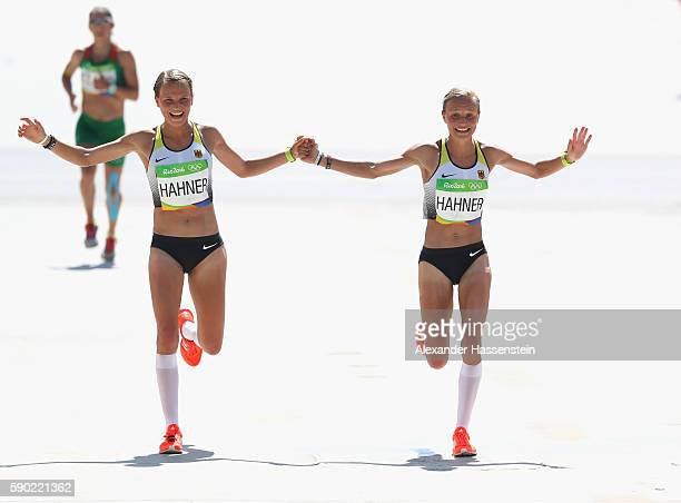 Anna Hahner of Germany and her sister Lisa Hahner reacts as thei approaches the finish line during the Women's Marathon on Day 9 of the Rio 2016...