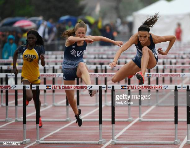 Anna Hall right Valor Christian leaps over the last hurdle on her way to winning the 4A 100 meter hurdles against teammate Destiny Grimes center and...