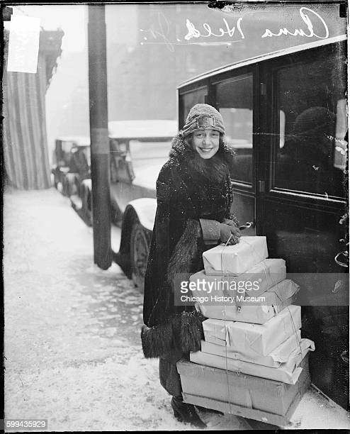 Anna Held holding a large stack of wrapped packages and standing on the street in the snow next to an automobile 1920s