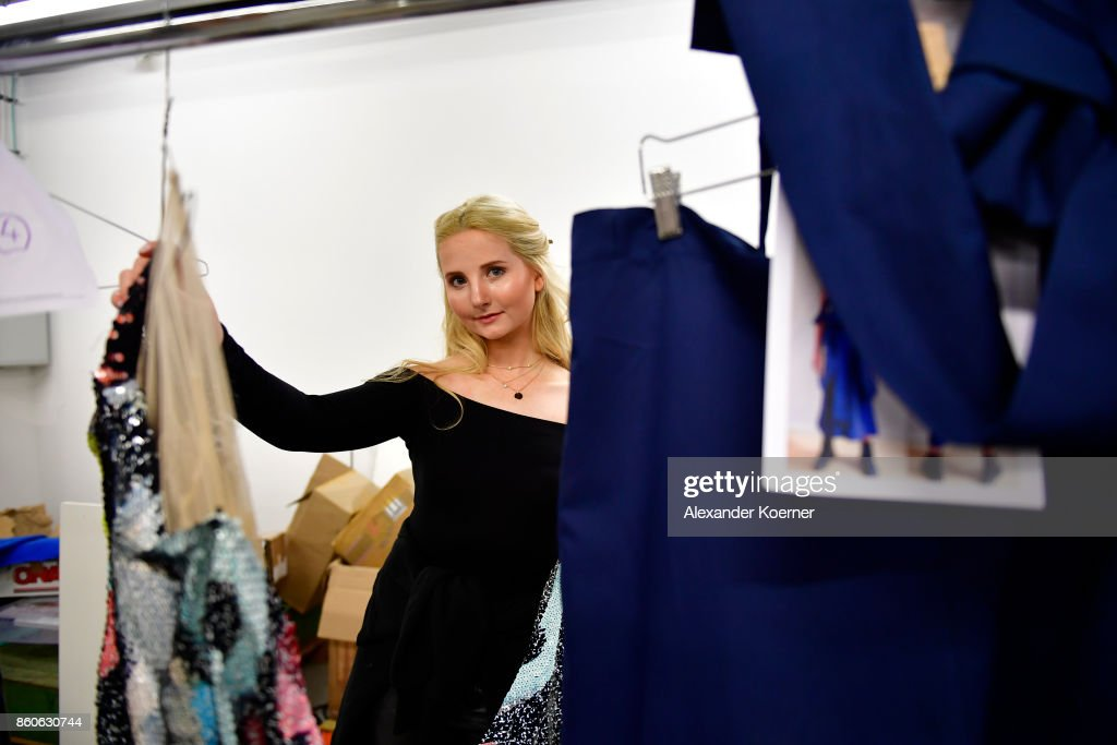 Anna Hiltrop takes a closer look to her outfit prior walking the runway during the American Women's Club And Esmod Charity Fashion Show at DRIVE. Volkswagen Group Forum on October 12, 2017 in Berlin, Germany.