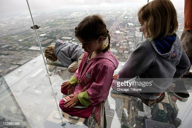 Anna Kane of Alton Illinois top left Sophie Allaway of Glen Ellyn Illinois and Grace Kane of Alton stare down the Sears Tower from 'The Ledge' at the...