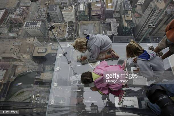 Anna Kane of Alton Illinois top Sophie Allaway of Glen Ellyn Illinois and Grace Kane of Alton stare down the Sears Tower from The Ledge on the Sears...