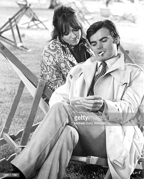 Anna Karina looks over JeanClaude Drouot's shoulder as he show her something in a scene from the film 'Laughter in the Dark' 1969