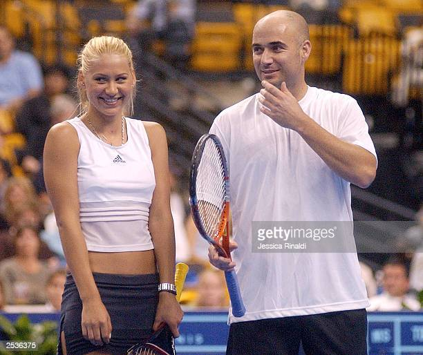 Anna Kournikova and Andre Agassi laugh together during a doubles tennis match on September 25 2003 at the Fleet Center in Boston MA Kournikova and...
