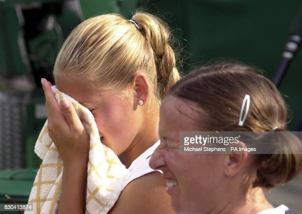 Anna Kournikova and doubles partner Natasha Zvereva hide their faces as a male streaker runs onto Court 14 at the Lawn Tennis Championships 2000 at...