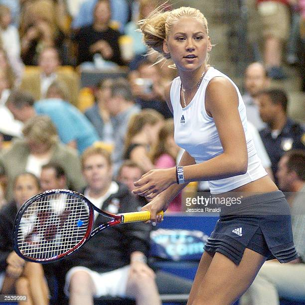 Anna Kournikova keeps an eye on her doubles partner Andre Agassi during a tennis match on September 25 2003 at the Fleet Center in Boston MA...